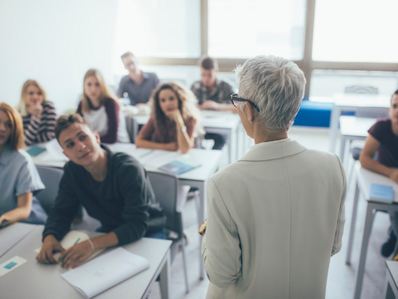 Back,View,Of,Grey-haired,Woman,Teacher,Stading,At,Classroom,And